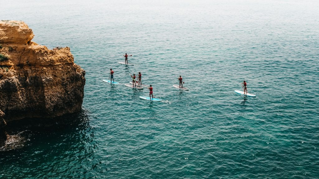 A group of people paddle boarding on the sea, next to a cliff. (This is actually a stock photo from Portugal but nobody knows!)