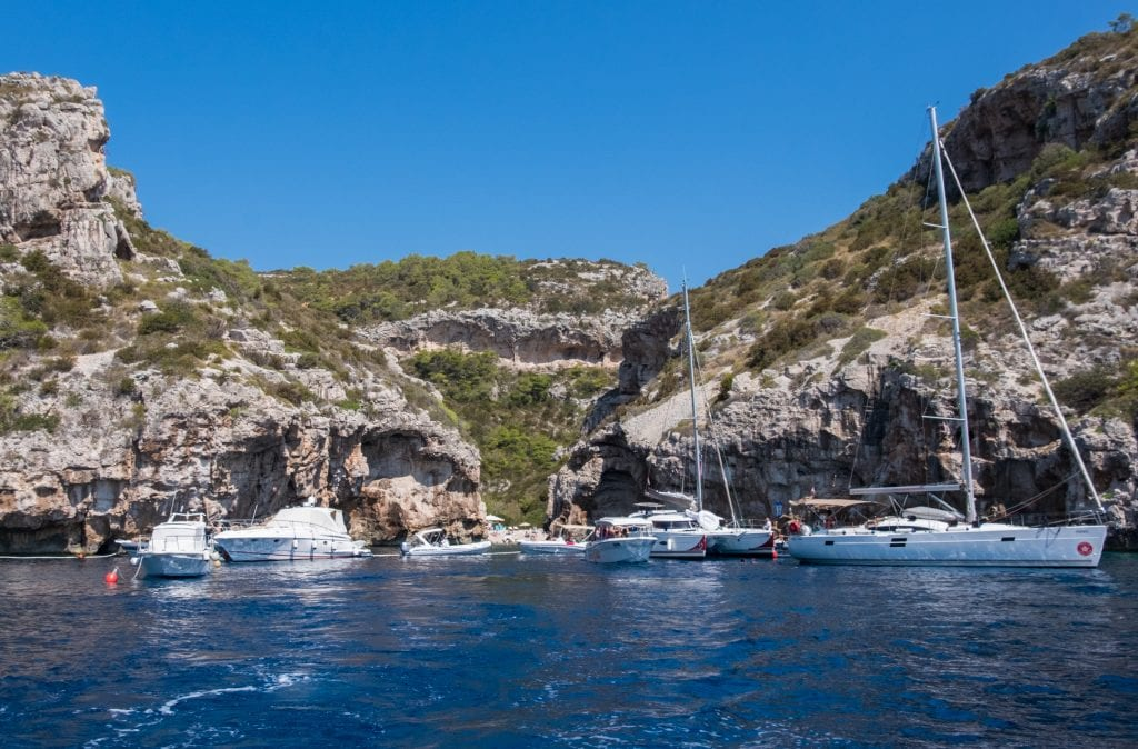 Several sailboats clustered around a narrow opening in two rocky cliffs leading to a beach.