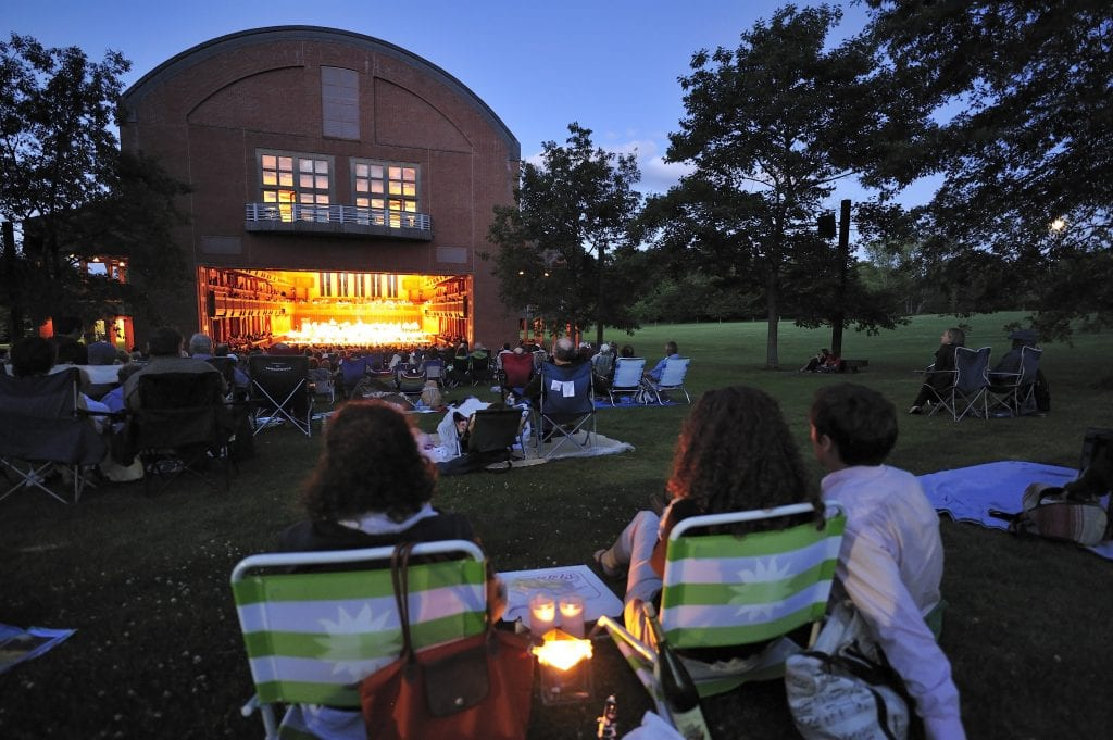The red brick theater of Tanglewood with a big open door; in front of it are people sitting in lawn chairs, listening to the music on a summer night.