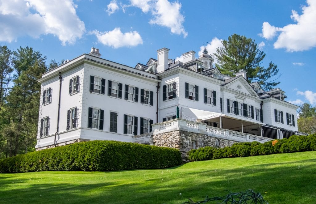The Mount: an enormous white mansion with dark green shutters and a small porch overlooking the landscape.