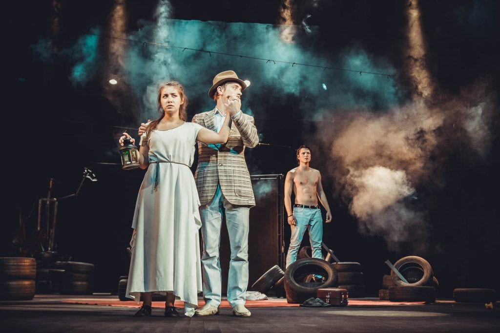A scene from a play, a man in a hat and blazer holding the hand of a woman in a nightgown holding a lantern. For some reason there's a shirtless dude in the background and I'm not complaining.