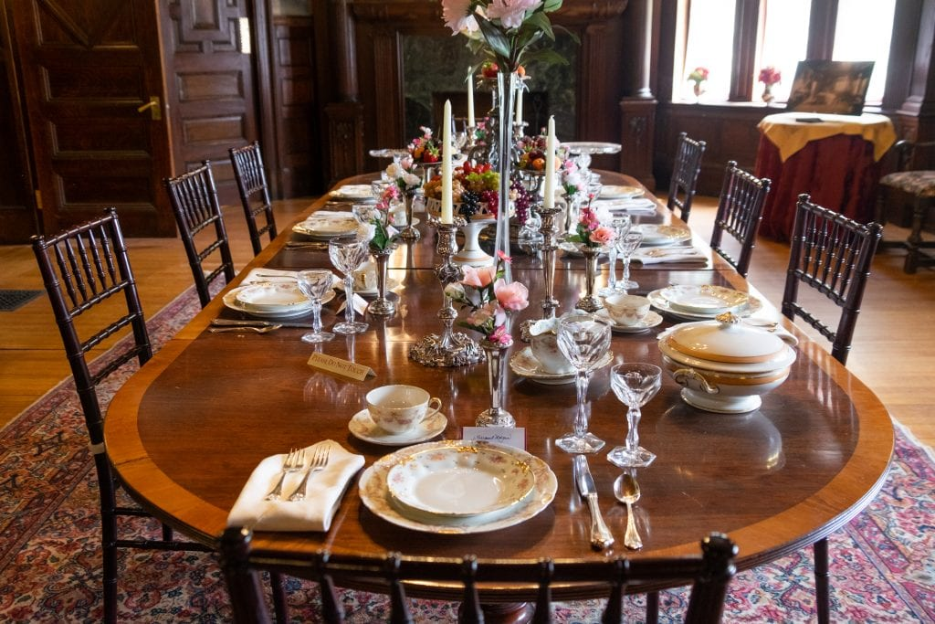 A fully set dining table at Ventford hall covered with gold-tipped china, crystal glassware, silver candlesticks, and silver vases filled with pink fake flowers.