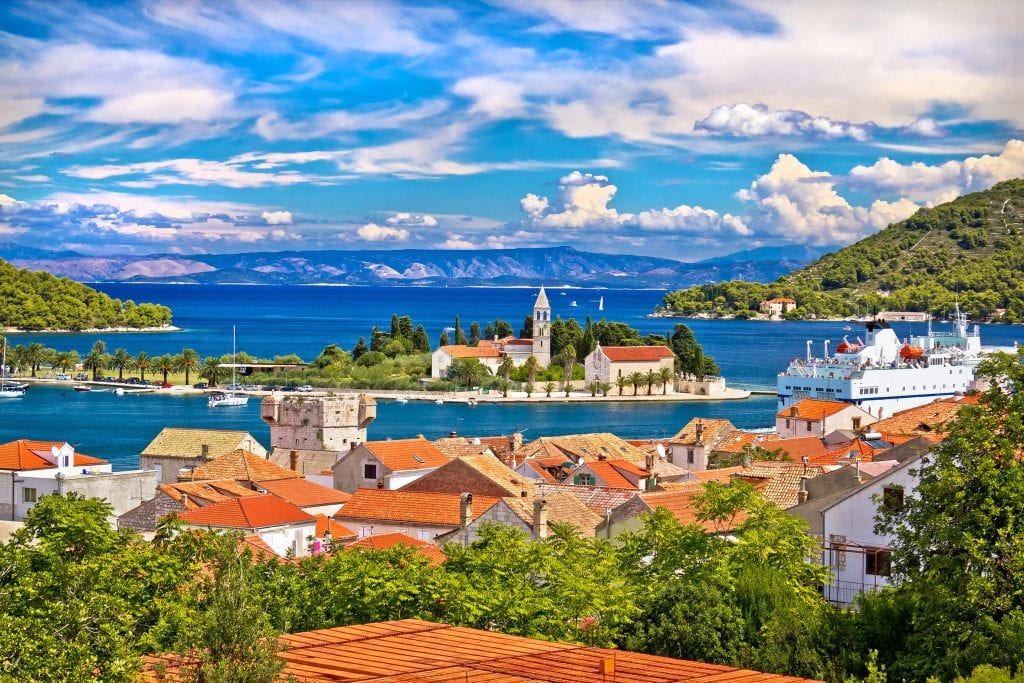 A view over Vis town: you see a small island in the harbor with a church tower, and in the foreground, lots of orange roofs, a ferry, and lots of green trees.