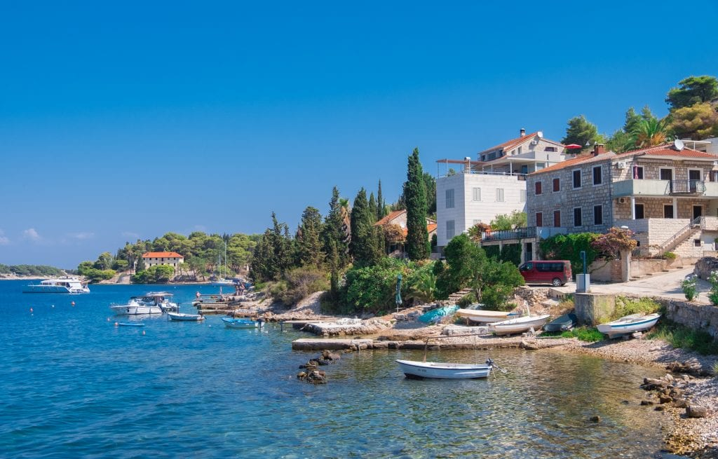 The waterfront in Kut, Vis: several stone buildings along the water's edge, small cement piers jutting into the water, and several small white boats moored in the water.
