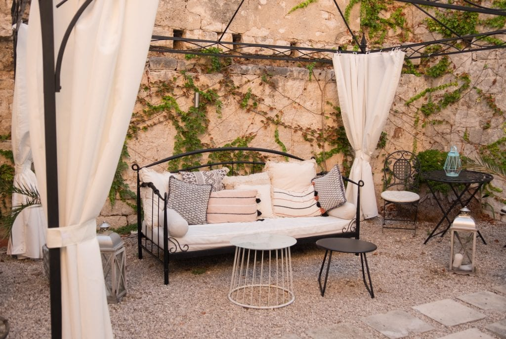 A wrought iron couch covered with beige cushions, surrounded by curtains, in the middle of an outdoor courtyard, the walls covered with ivy.