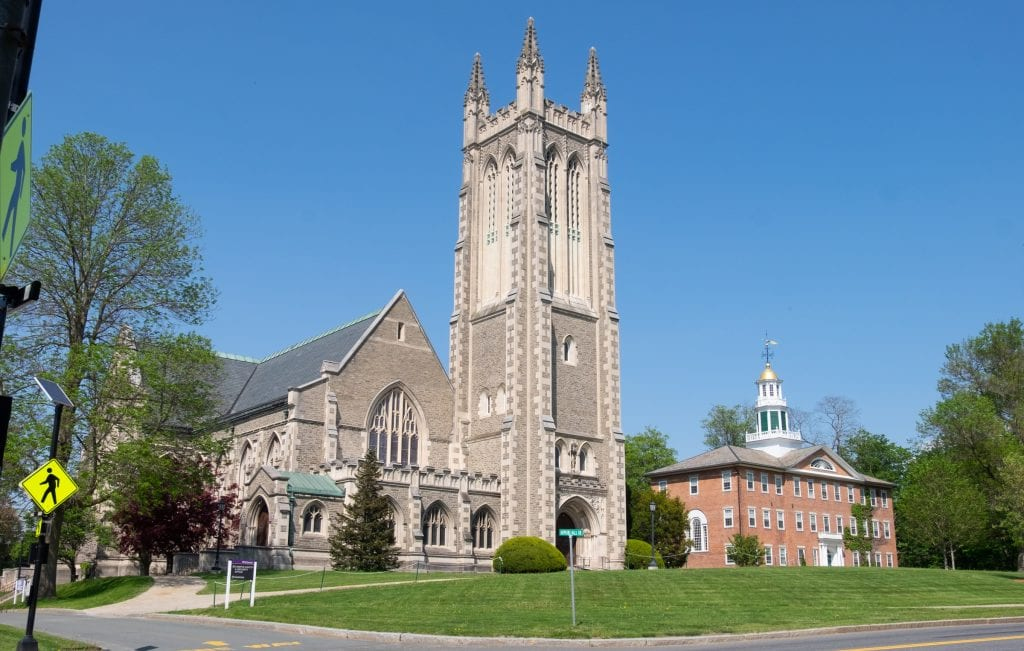 Two buildings in the tiny town of Williamstown: a big gray church with a tall bell tower, and a smaller red brick building with a tiny gold dome and weathervane.