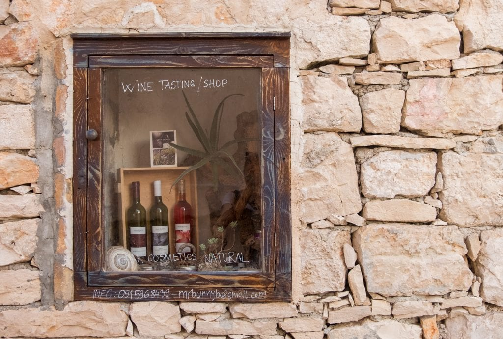 """A rock wall in Vis town, with a window that has wine bottles inside and reads """"Wine Tasting/Shop."""""""