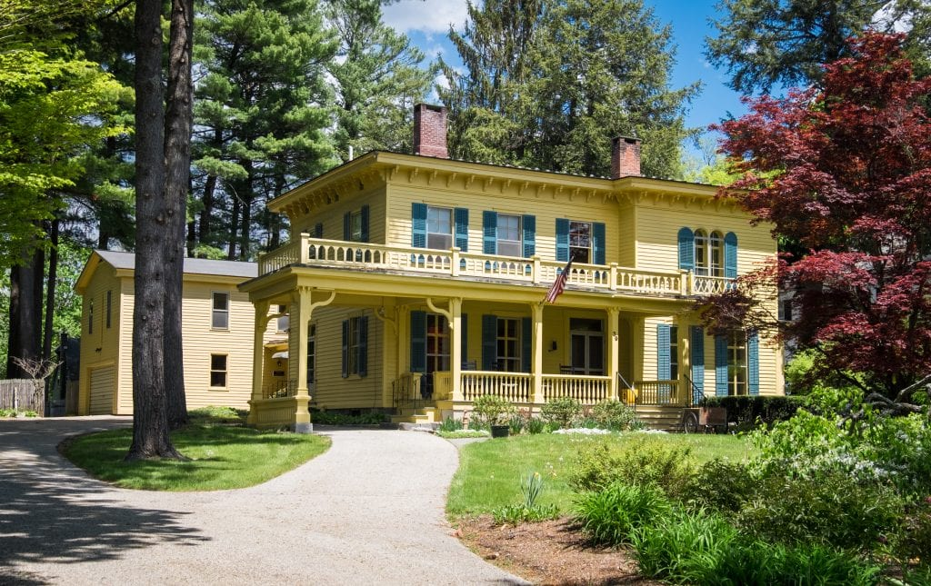 A bright yellow old-fashioned house with a wraparound porch set amongst a wooded area.