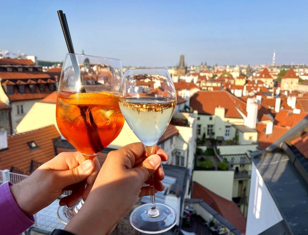 Two glasses clinking together in cheers, an aperol spritz and a glass of champagne, overlooking the orange roofs of Prague at sunset.
