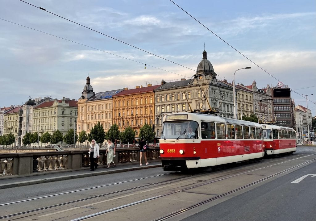 Prague at sunset: you see crenellated buildings on the edge of the river in shades of cream, orange and pale green. In the foreground, a bridge with a red tram going down the street.