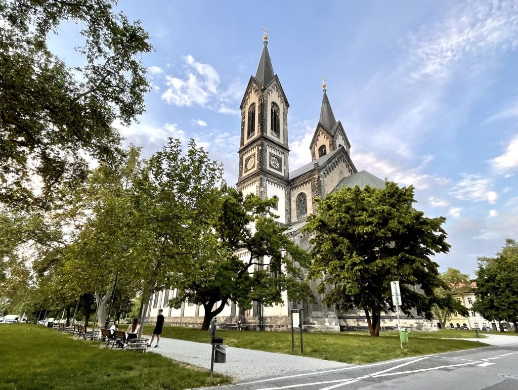 The large gothic church in Karlín, Prague, surrounded by a park and trees flush with leaves.