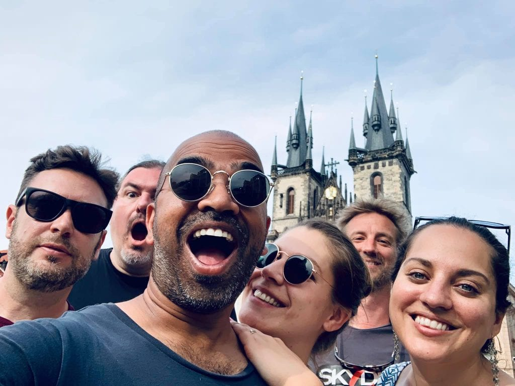 A group selfie of friends in front of the steeples of a church in front.
