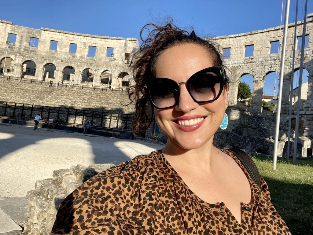 Kate posing for a selfie, standing in the middle of a Roman amphitheater in Pula, Croatia; it looks like the Colosseum of Rome. Kate has her hair up and wears sunglasses and a leopard-print button-up t-shirt.