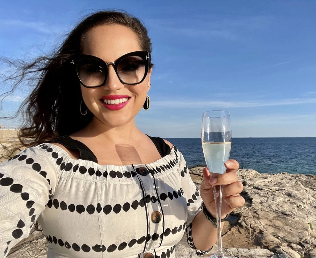 Kate glamour selfie. Kate wears a white off the shoulder Derek Lam top with black polka dots, oversized black Tom Ford sunglasses, gold-edged black Kendra Scott drop earrings, and hot pink lipstick. She holds a glass of champagne and stands on a rocky beach in Croatia.
