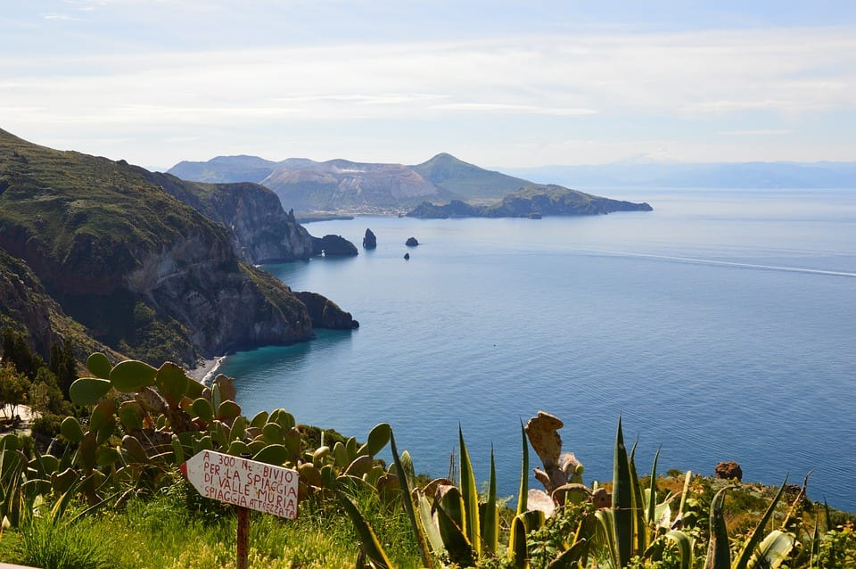 A view overlooking Lipari, one of the Aeolian Islands: A tall, volcanic island coming out of the sea, with lots of tall cliffs. In the foreground, lots of cacti and a hand-painted sign directing to the beach (Spiaggia).