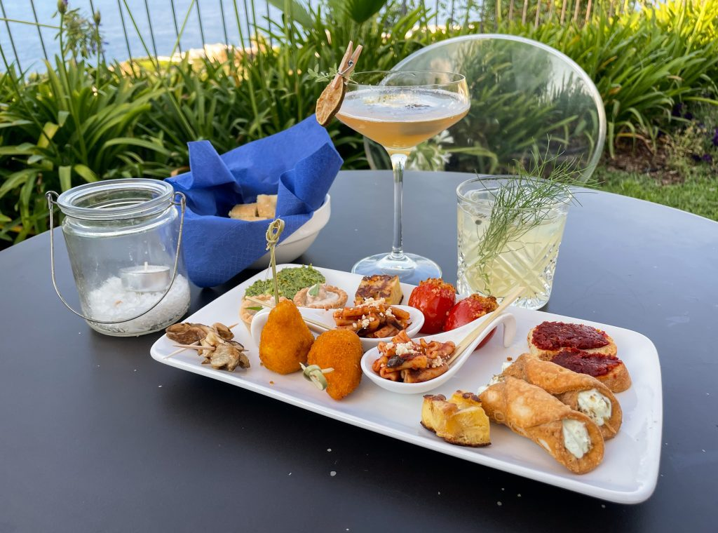 Two cocktails next to an aperitivo plate for two, topped with crostini, spoons filled with pasta alla norma, arancini, stuffed tomatoes, mini cannolis, and other goodies.