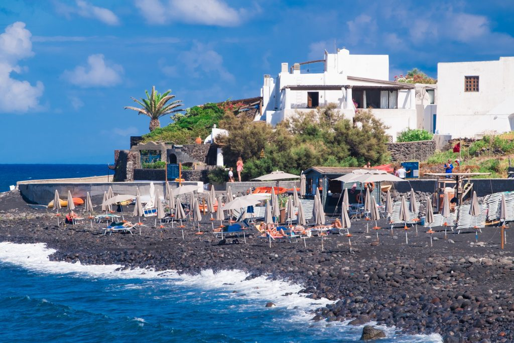 A gray rocky beach topped with umbrellas and chairs next to them on Ficogrande on Stromboli.
