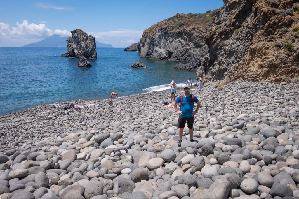 Charlie standing on giant gray rocks, nearly boulders, each about 12 inches wide, in Cala Junco, Panarea.