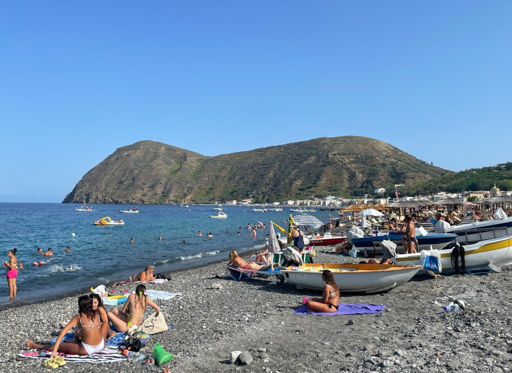 Canneto Beach, a long and overcrowded gray beach with lots of people, kids, floats, boats, and umbrellas.