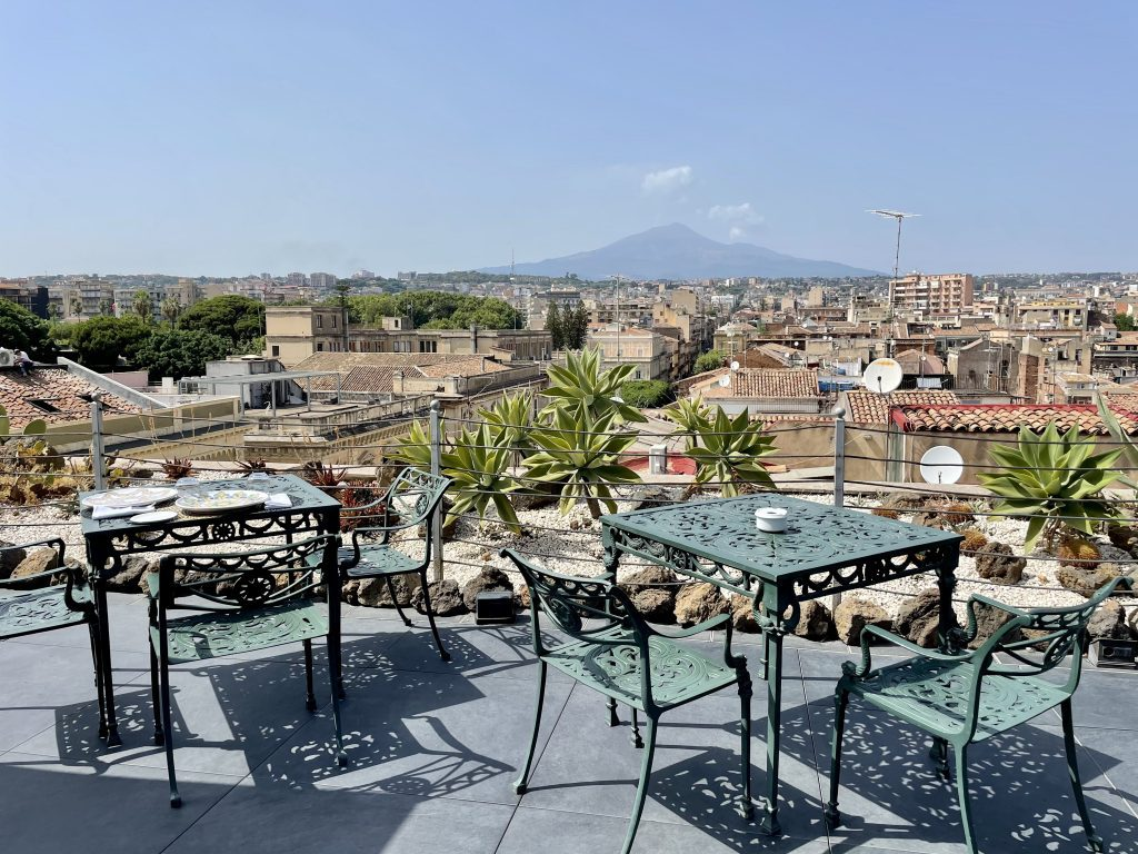 An outdoor terrace with wrought iron tables and chairs overlooking the orange roofs of Catania, with Mount Etna in the distance.