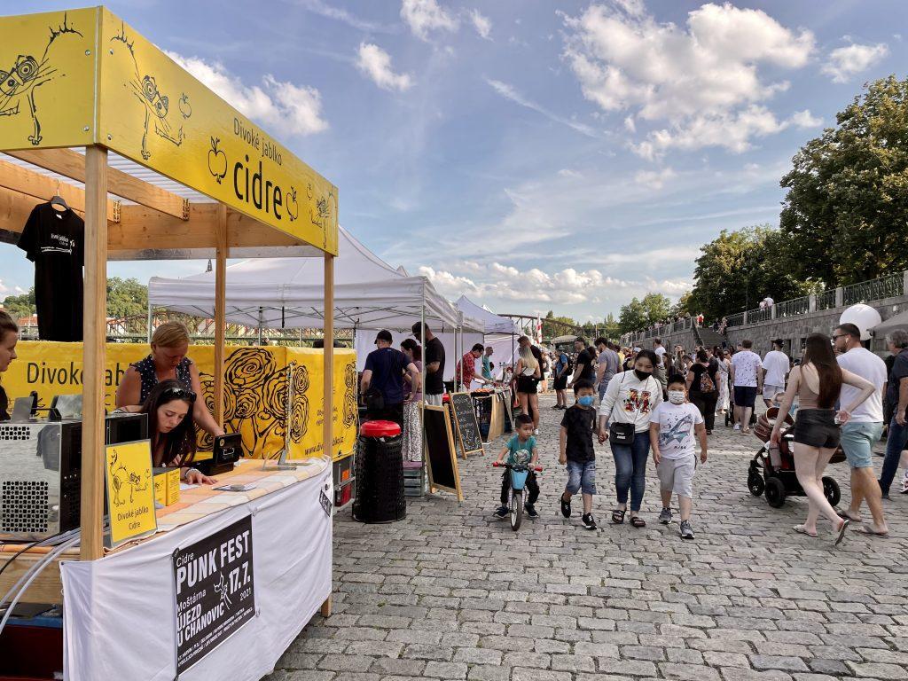 A crowd of people along the riverside in Prague, buying cider at cider stands for Cider Fest.