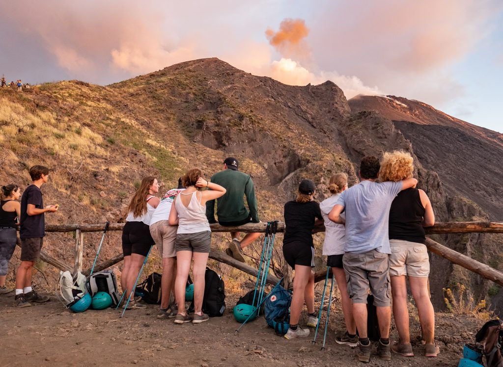 A group of hikers standing in front of a wooden fence, the volcano of Stromboli at sunset emitting pink smoke.