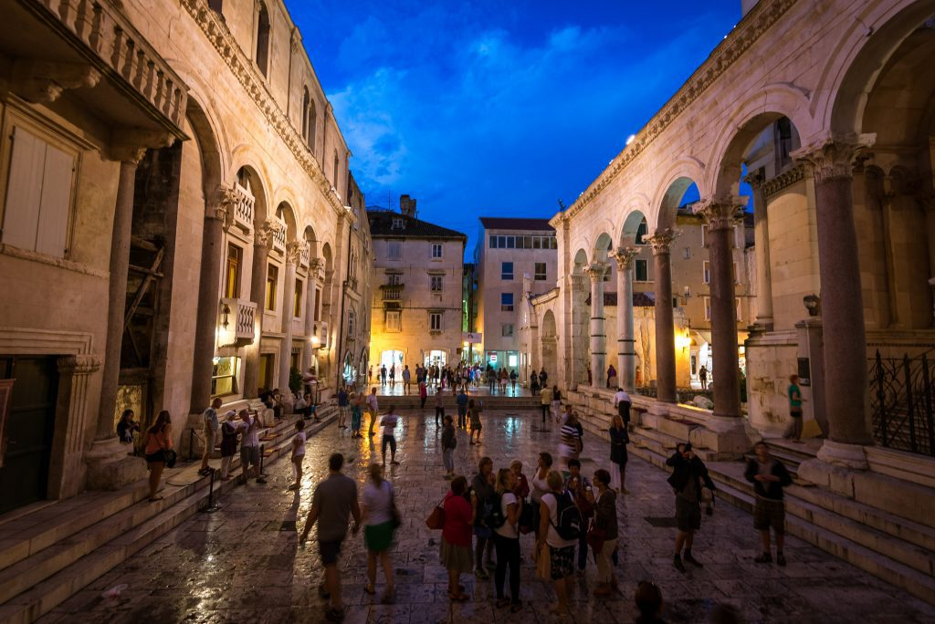 Diocletian's Palace at night: rising columns on stone buildings on each side, with dozens of people walking around in the middle.