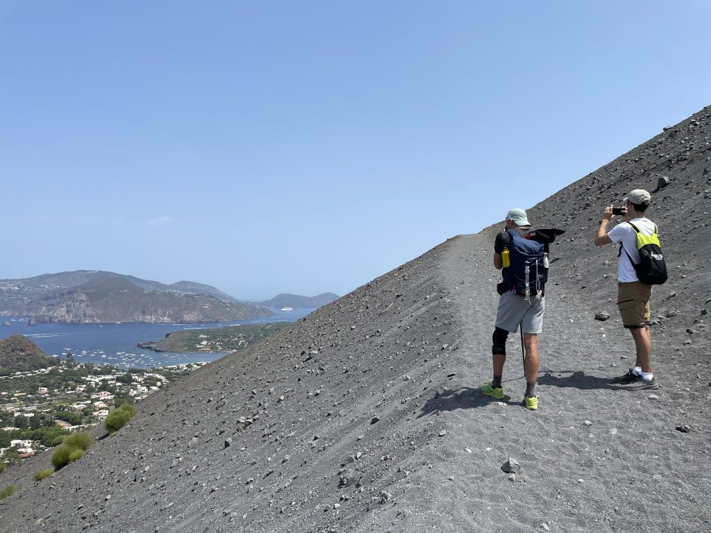 Two men taking a photo while climbing the gray sandy volcano of Vulcano, overlooking islands in the distance.