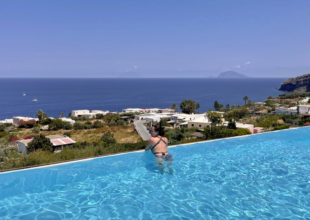 Kate leaning on the edge of the Infinity pool at Hotel Ravesi, overlooking green hills, the ocean, and two islands in the distance.