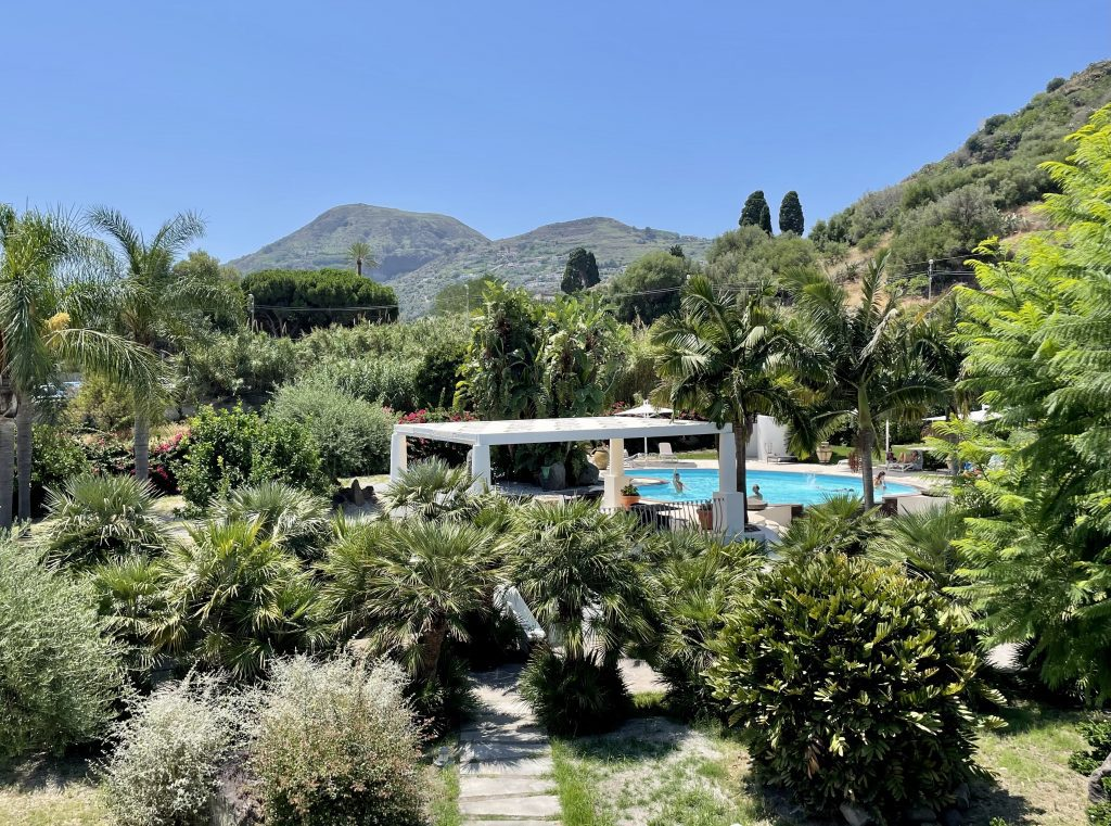 The grounds of Hotel Residence La Giara: a lush green outdoor area with lots of trees and bushes, and in the distance, a small swimming pool filled with kids.
