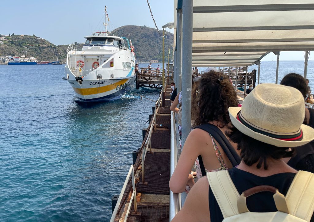 A line of people on a pier waiting to boars a small white hydrofoil named Carmine.