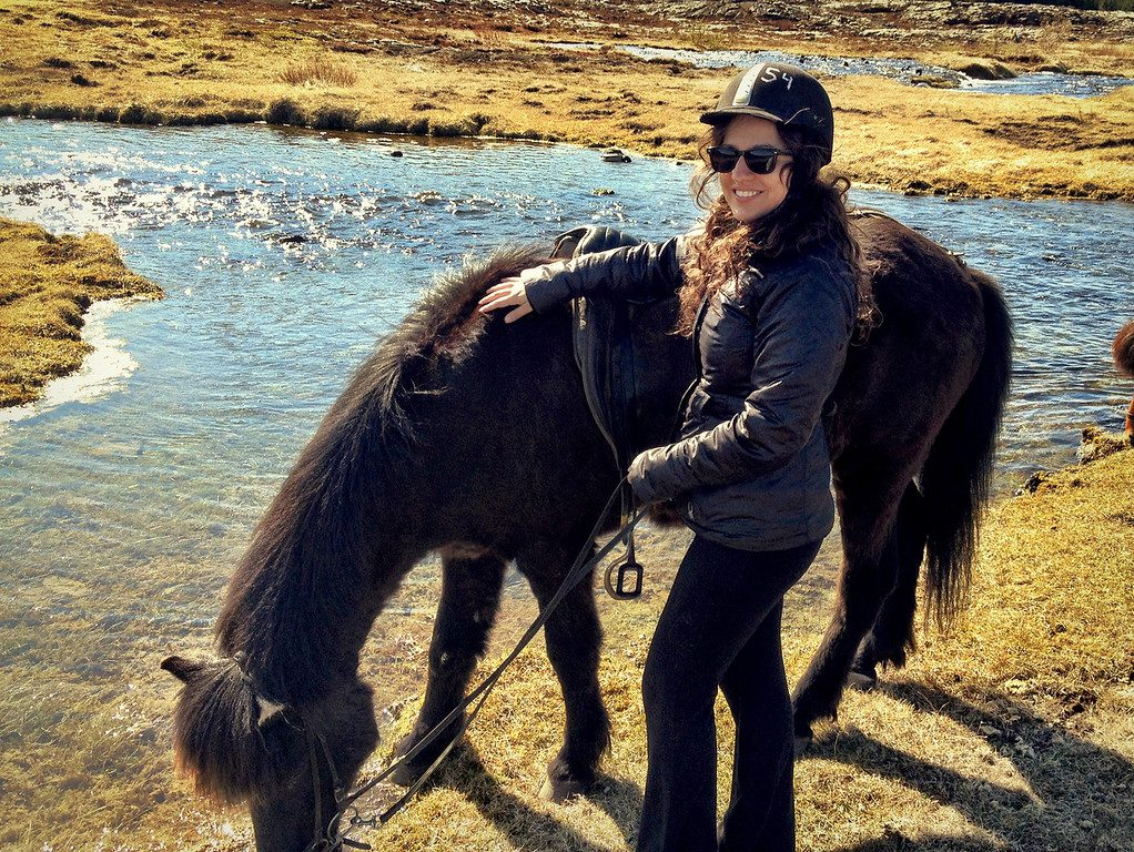 Kate stands smiling next to a dark Icelandic horse, bending his head down to drink from a stream.