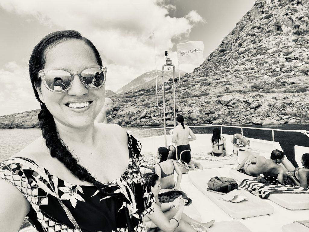Kate taking a selfie on a boat in Sicily, wearing sunglasses and her hair in a braid. Behind her, people are sunbathing on the boat's top deck; behind that, rocky islands.