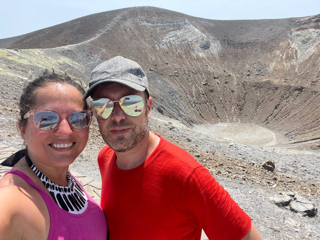 Kate and Charlie taking a sweaty selfie in front of the crater of Vulcano, pale gray-brown, almost like a lunar landscape.