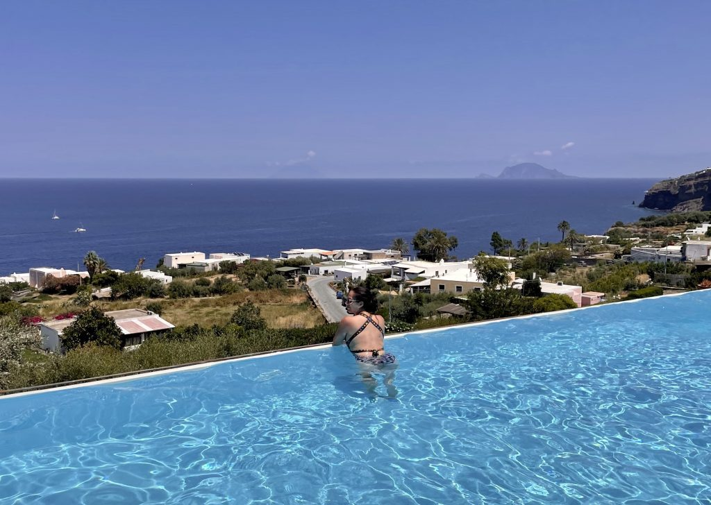 Kate on the edge of the infinity pool at Hotel Ravesi, overlooking the green island landscape with palm trees and white buildings. In the distance in the ocean you can see two islands: Stromboli and Panarea.