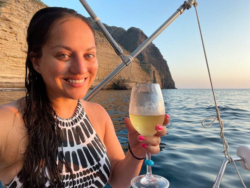 A selfie of Kate smiling with a glass of white wine, wearing a black and white patterned bathing suit. She's on a boat, her hair is long and wet, and you can see Pollara's cliffs behind her.