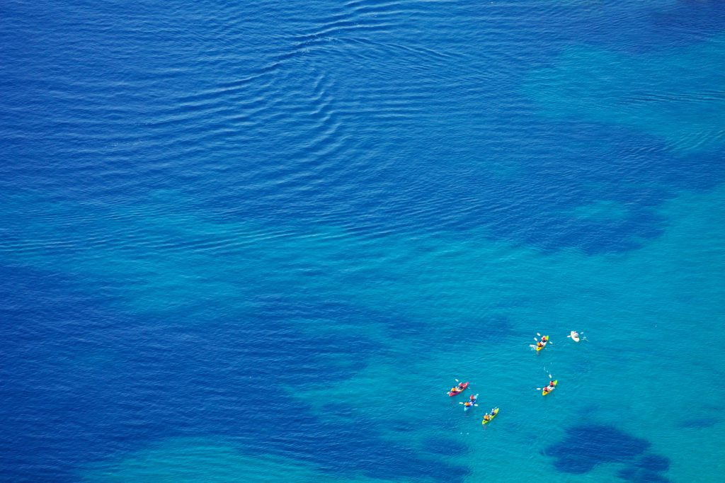 An aerial shot of several kayakers in the bright blue sea.