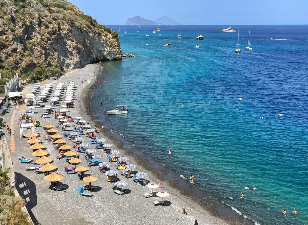 White Beach in Lipari, with rows of umbrellas with seats next to them. A pebbly gray beach leading to bright blue-green water, several people and small white boats in the water.
