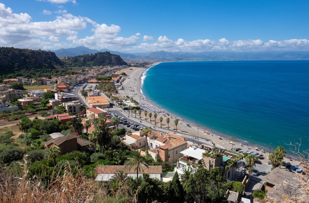 Milazzo: on the right, a half-moon of calm gray beach next to bright blue water. On land, houses and vegetation, and in the background, you see what look like small mountains (the ridge), one topped with the ruins of a castle.