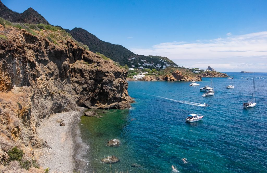 View of tall brown cliffs of Stromboli, small gray pebbly beaches, and several sailboats docked in the bright blue-green water.