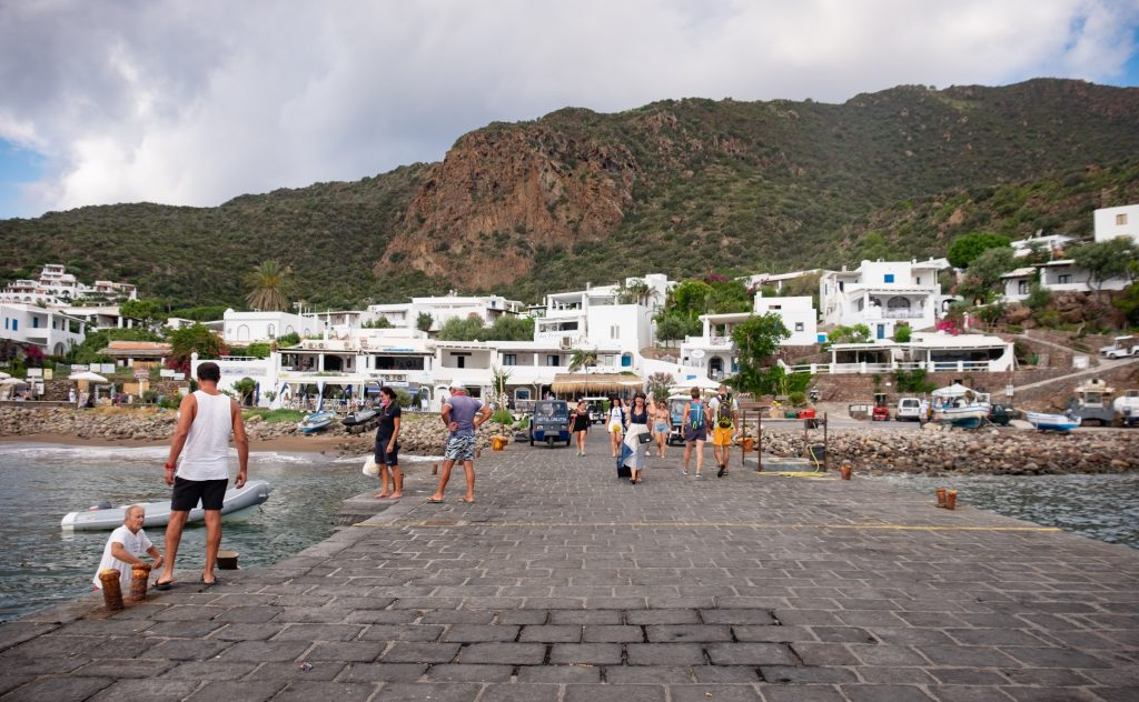 The dock of Panarea: a long gray brick pier leading to a small town filled with blocky white buildings. People dragging suitcases to the dock to get on the ferry.