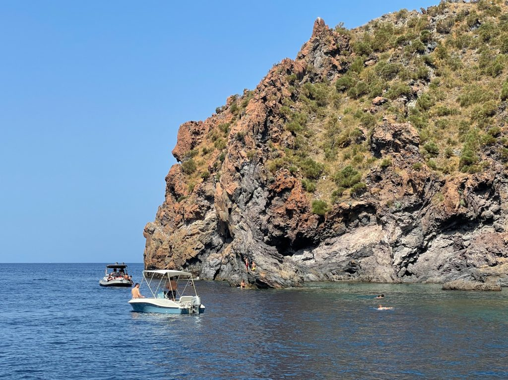 On the red-brown coast of Vulcano, you see a small pool that is clearer and greener than the other ocean water, and some people swimming and boating near it.