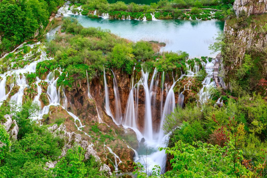 Dozens of waterfalls springing from the edge of a lake atop a cliff.
