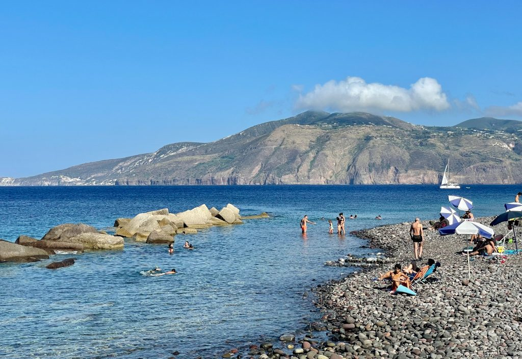 Punta Lingua, a small beach with large but not huge gray rocks leading into clear shallow water, a few kids and adults in the water. Lipari island is in the distance.