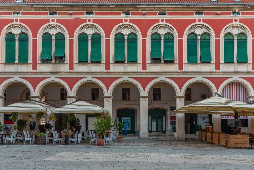 Republic square with its light red walls, emerald green shutters, and rows of porticoes along the bottom, cafe tables in front.