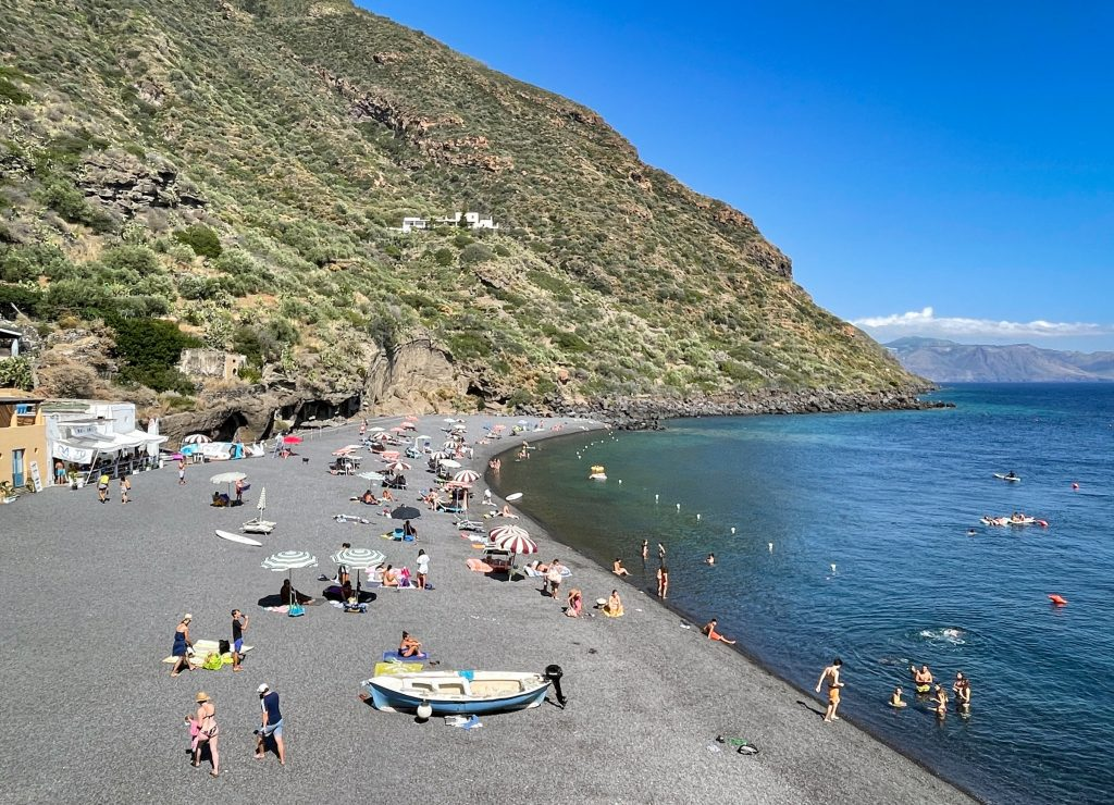 Rinnella Beach with a few dozen people on it. You see small gray stones, very calm teal water with almost no waves. Lots of kids there.