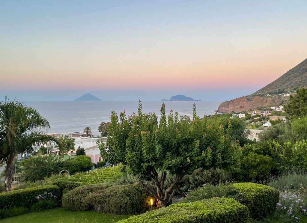 Views of green landscaping of Salina, cliffs in the distance, and you see the islands of Stromboli and Panarea peeking above the coastline as the sun sets.