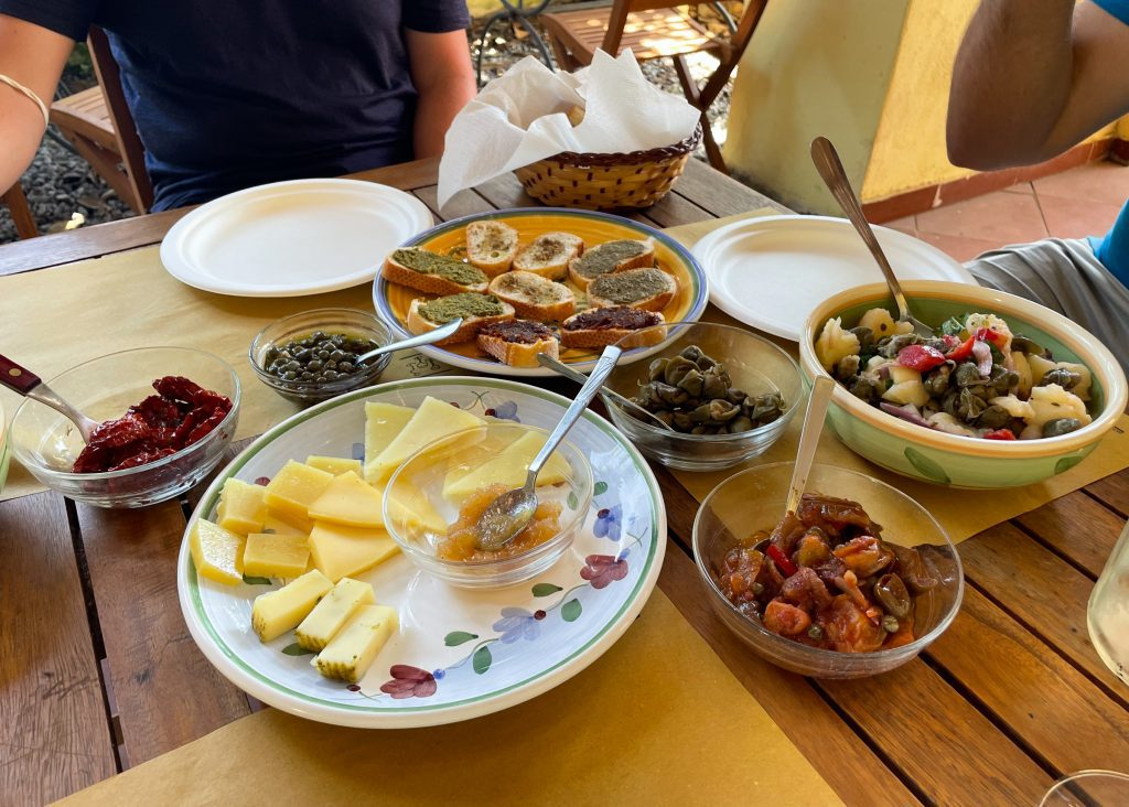 Plates and platters of capers, sun-dried tomatoes, several cheeses with honey, crostini with all kinds of spreads, and Aeolian potato salad with capers and tomatoes.