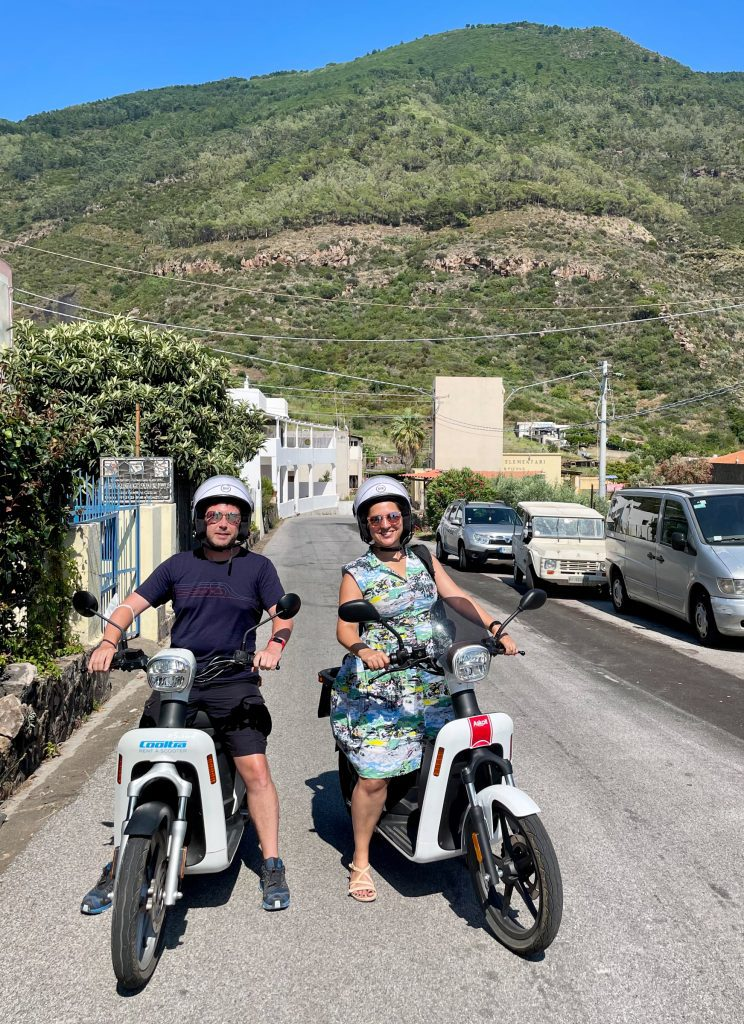 Kate and Charlie side by side on white electric motorbikes, a green mountain rising behind them. Kate wears a 50s-style green and white patterned housewife dress.