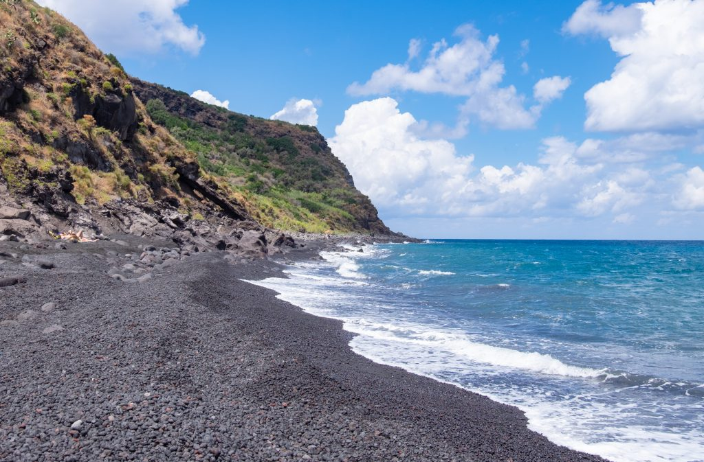 Beautiful Spiaggia Lunga, a sparkling black sand beach with bright blue waves, tall green cliffs in the distance. If I didn't know where this was taken I would guess Hawaii.